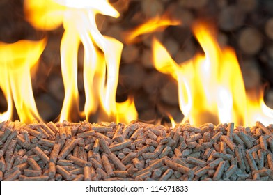 Oak Pellets in  flames- chopped firewood background