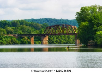 Oak Ridge, Tennessee, USA - July 14,2018:  View from the shores of Melton Lake Park in Oak Ridge, Tennessee.  Two men in a kayak skim the waters as they head toward a distant bridge.