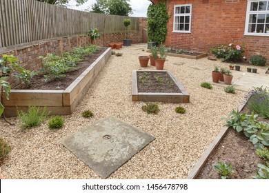Oak sleeper raised beds in a courtyard garden design with hard landscpaing, gravel and terracotta pots