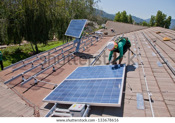 OAK VIEW - OCTOBER 10: Workers install solar panels on the roof of a house on October 10, 2011 in Oak View, Southern California