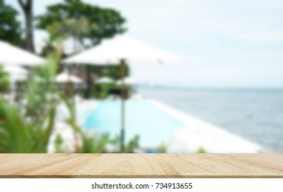 oak wood Table Top with Blur luxury outdoor swimming pool with sea view Background. Happy hour good view on vacation on holiday