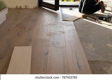Oak-colored parquet boards lined up during installation on the floor of an apartment under renovation. Worker at work