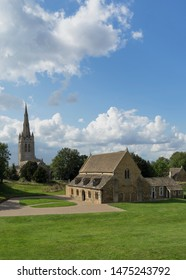 Oakham Castle on a beautiful day with the All Saints Church in the background in Oakham, Rutland, United Kingdom.
