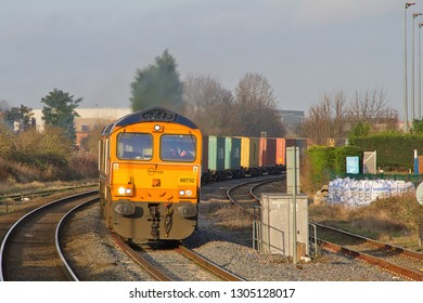 OAKHAM, RUTLAND, UK - JANUARY 5, 2013: GBRf Class 66 No. 66732 'GBRf The First Decade 1999 - 2009 John Smith MD' rounds the curve approaching Oakham with the 4L20 12:44 Hams Hall to Harwich intermodal