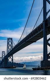 Oakland Bay bridge with sailing boat underneath