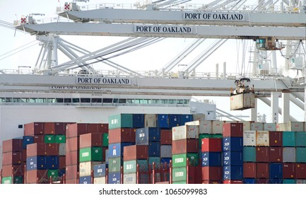 Oakland, CA - April 09, 2018: Cargo Ship APL DETROIT loading at the Port of Oakland, close up on crane with container. Crane operators can move an average of 30 containers per hr on or off the ships.