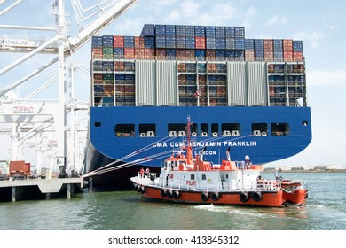 Oakland, CA - April 26, 2016: Pilot vessel DRAKE pulling up to the dock at the Port of Oakland Middle Harbor Terminal behind CMA CGM BENJAMIN FRANKLIN. Crew standing on the deck.