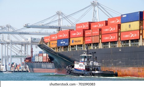 Oakland, CA - August 16, 2017: Tugboat LIBERTY off the port bow of cargo ship SEASPAN LONCOMILLA, assisting the vessel to maneuver into the Port of Oakland.