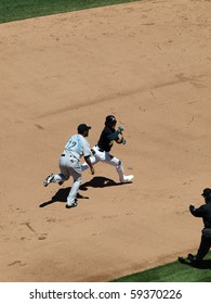 OAKLAND, CA - AUGUST 18: Blue Jays vs. Athletics: Athletics Coco Crisp is ran after by Blue Jays SS Yunel Escobar during a run down play.  Taken on August 18 2010 at Coliseum in Oakland California.