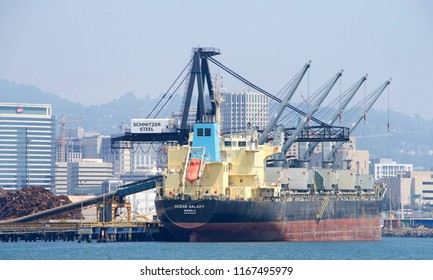 Oakland, CA - August 19, 2018: Bulk Carrier OCEAN GALAXY loading at Schnitzer Steel at the Port of Oakland. SchnitzerSteel recycles scrap metal into finished steel products such as rebar and wire rod