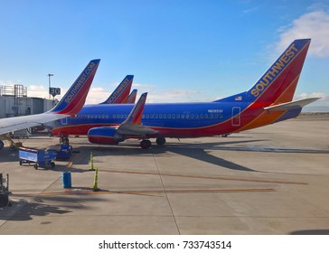 OAKLAND, CA - DECEMBER 25, 2015: A Southwest Airlines 737-300 sits alongside other Southwest aircraft at OAK. In October 2017, Southwest announced it would start selling tickets to Hawaii in 2018.