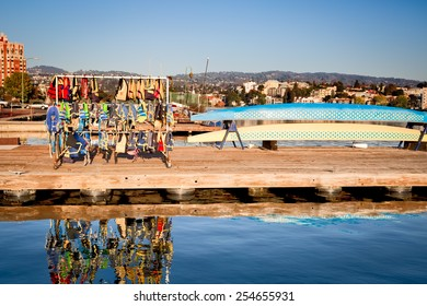 Oakland CA downtown Lake Merritt dock with rowing sculls and a rack of colorful life vests. Golden afternoon light.