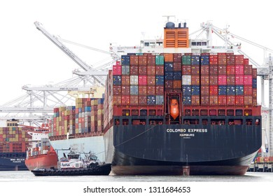 Oakland, CA - February 11, 2019: Cargo Ships are unable to maneuver sideways. Multiple tugboats assist cargo ship COLOMBO EXPRESS to maneuver to the dock at the Port of Oakland.