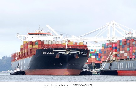 Oakland, CA - February 15, 2019: Multiple tugboats assisting Cargo Ship MSC JULIE to enter the Port of Oakland, the fifth busiest port in the United States.
