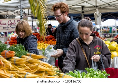 OAKLAND, CA - JAN. 11, 2014: Shoppers select fresh produce at the Grand Lake Farmers Market, open Saturdays year around and one of the largest in the region. More than 100 farmers participate.