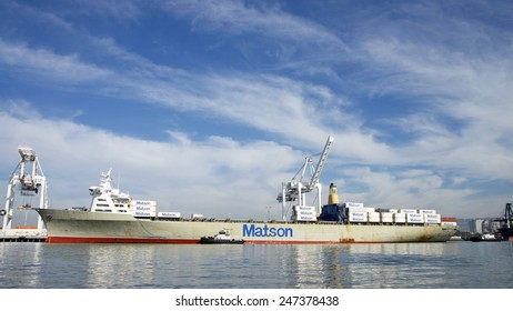 OAKLAND, CA - JANUARY 26, 2015: Matson Cargo Ship MANOA is guided into the Port of Oakland by Tugboat REVOLUTION off the port side and Tugboat PATRICIA ANN at the Stern.