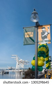 """OAKLAND, CA - JANUARY 26, 2019: Light pole banner that reads, """"Rooted in Oakland"""" at Jack London Square promoting the Oakland Athletics, with cargo cranes at the Port of Oakland in the background."""