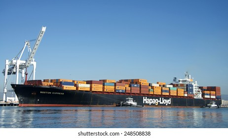 OAKLAND, CA - JANUARY 30, 2015: Hapag-Lloyd Cargo Ship BOSTON EXPRESS entering the Port of Oakland with Tugboat Assist. Hapag-Lloyd is a German transportation company.