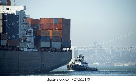 OAKLAND, CA - JANUARY 30, 2015: Tugboat Z-FIVE at the Stern of Hapag-Lloyd Cargo Ship BOSTON EXPRESS as it enters the Port of Oakland. Hazy skies dim the San Francisco Skyline in the background.