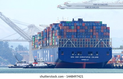 Oakland, CA - July 08, 2019: Multiple tugboats assist the behemoth vessel CMA CGM CRISTOPHE COLOMB to maneuver sideways to the docks at the Port of Oakland.