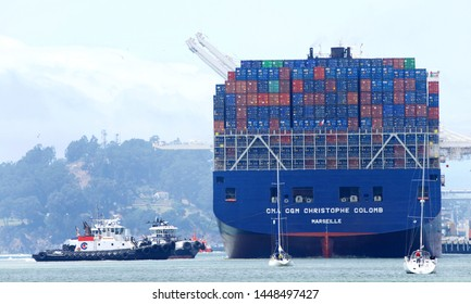 Oakland, CA - July 08, 2019: Tugs move vessels that should not move themselves, such as ships in a crowded harbor. Multiple tugboats assist CMA CGM CHRISTOPHE COLOMB to maneuver sideways to the docks.