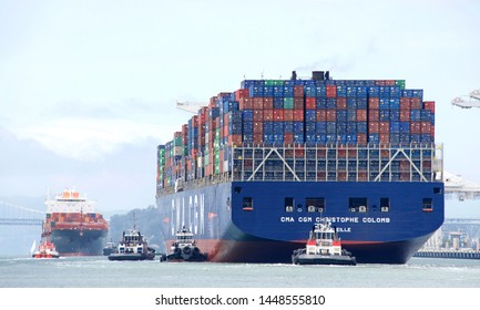 Oakland, CA - July 08, 2019: Tugboats assist CMA CGM CRISTOPHE COLOMB to maneuver sideways to the docks at the Port of Oakland while TOKYO EXPREsS also enters the Port