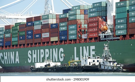OAKLAND, CA - JULY 13, 2015: China Shipping Lines Cargo Ship SUMMER loading at the Port of Oakland with Tugboat ROYAL MELBOURNE securing a barge ship up beside the vessel to provide maritime services.