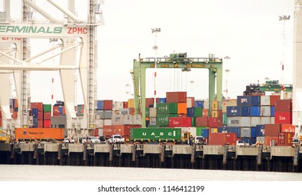 Oakland, CA - July 30, 2018: Stacks of shipping containers line the docks at the Port of Oakland, awaiting Cargo Ships to transport them. Truck transporting container to waiting ship for loading.