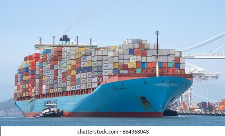 Oakland, CA - June 06, 2017: Multiple tugboats assist cargo ship GUDRUN MAERSK to maneuver into the Port of Oakland. Maersk is the world's largest container shipping company.