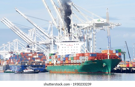 Oakland, CA - Mar 5, 2021: Tugboat Z-THREE assisting cargo ship SEASPAN . HAMBURG to maneuver to the docks at the Port of Oakland, diesel exhaust spewing from the ships stack.
