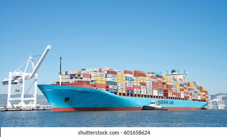 Oakland, CA - March 14, 2017: Tugboat DELTA BILLIE off the port side of CRETE MAERSK, assisting the vessel to maneuver into the Port of Oakland.