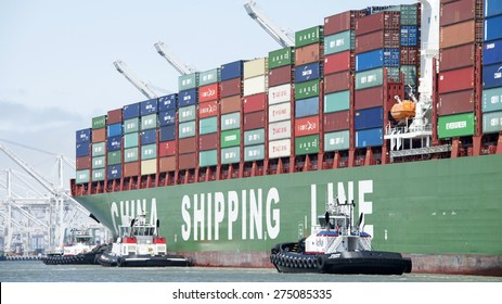 OAKLAND, CA - MAY 03, 2015:  China Shipping Lines Cargo Ship CSCL SPRING entering the Port of Oakland with multiple tugboats assisting the vessel to maneuver.