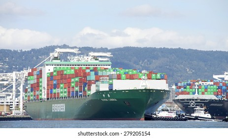 OAKLAND, CA - MAY 13, 2015: Tugboat REVOLUTION at the stern of Cargo Ship EVER LIBRA, assisting the vessel to depart the Port of Oakland.