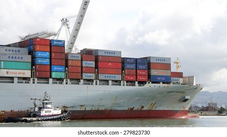 OAKLAND, CA - MAY 14, 2015: Cargo Ship COSCO INDONESIA entering the Port of Oakland with AmNav Tugboat LIBERTY assisting from the starboard side.
