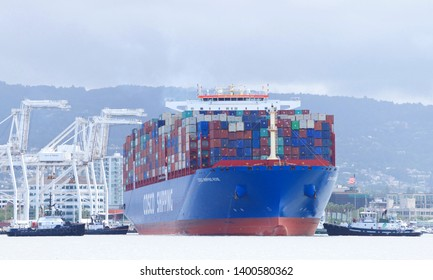 Oakland, CA - May 16, 2019: Multiple tugboats assisting Cargo Ship COSCO SHIPPING ROSE to maneuver out of the Port of Oakland, the fifth busiest port in the United States.