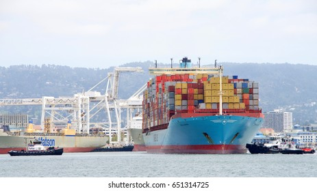 Oakland, CA - May 30, 2017: Multiple tugboats work together to push and pull cargo ship GERDA MAERSK, turning it 180 degrees prior to docking at the Port of Oakland.