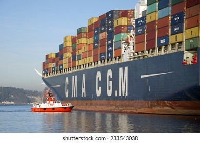 OAKLAND, CA - NOVEMBER 25, 2014:  P/V GOLDEN GATE PILOT on the port bow of CMA CGM LYRA assisting with the Cargo Ships departure from the Port of Oakland.