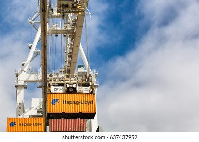 OAKLAND, CA- Oct 9, 2014: Oakland Port crane lifting cargo shipping containers. Close detailed view looking up. Blue sky and clouds with copy space.