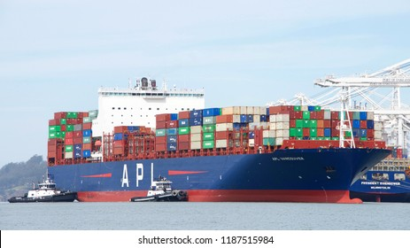 Oakland, CA - September 12, 2018: Tugboats are powerful for their size and strongly built. Multiple tugboats assist cargo ship APL VANCOUVER to maneuver into the Port of Oakland.