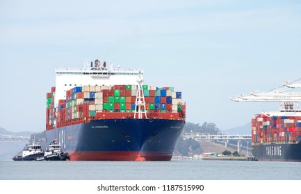 Oakland, CA - September 12, 2018: Tugboats assisting APL VANCOUVER to maneuver into the Port of Oakland. American President Lines (APL) is the worlds 7th largest container transportation shipping Co.