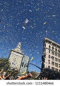 Oakland, CA / USA - June 12 2018: Golden State Warriors NBA Championship Parade, Photo of Blue and Yellow Confetti Falling from the Sky in Downtown Oakland