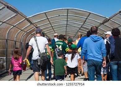 OAKLAND, CA-Aug. 22, 2012: Happy Oakland baseball fans leave the Coliseum after the Oakland Athletics beat the Minnesota Twins 5-1 on a sunny summer afternoon. People crowd through the pedestrian over