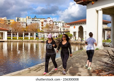 OAKLAND, CA-DEC 6, 2014: Women on the 3.4 mile path around Lake Merritt in downtown Oakland, popular with walkers and joggers. The historic pergola shown was built in 1913 and restored in 2007.