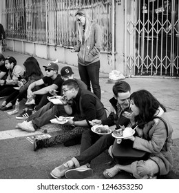 OAKLAND, CA-June 6, 2014: Millenials at the Art Murmur uptown gallery hop, sit on the sidewalk eating bbq sold on the street. The scene draws visitors from all over the Bay Area. Gritty urban setting.