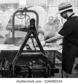 OAKLAND, CA-June 6, 2014: Street chef at Art Murmur cooks bbq on an industrial strength grill. Gritty urban setting. Black and white square format.