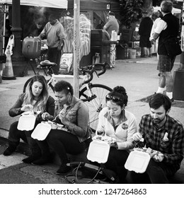 OAKLAND, CA-June 6,2014: Millenials sit on the curb eating street food at the city's monthly Art Murmur uptown gallery hop. Street chefs grill barbecue in the background. Gritty urban setting.