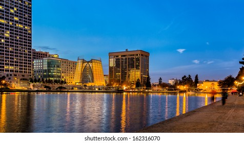 "Oakland, California. Evening view across Lake Merritt with reflections of buildings and lights on the water. The ""Necklace of Lights"" illuminates the pedestrian walk around the lake. Copy space."
