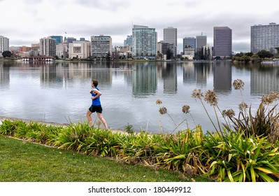 OAKLAND, CALIFORNIA - JAN. 11, 2014: A jogger runs on the 3.4 mile path around Lake Merritt in downtown Oakland.The shoreline was recently renovated, adding new parks and an amphitheater.