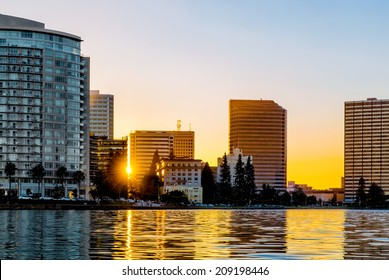 Oakland Lake Merritt waterfront buildings backlit at sunset with sun flare and reflections on the lake. Viewed from the water. Copy space.