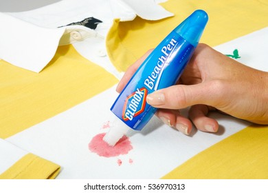 OAKLAND, USA - JUL 07, 2005: Clorox Bleach Pen Held by a woman's hand being used on a stained shirt illustrative editorial